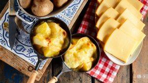 Köstlicher traditioneller Schweizer Raclettekäse auf gewürfelter gekochter oder gebackener Kartoffel.
